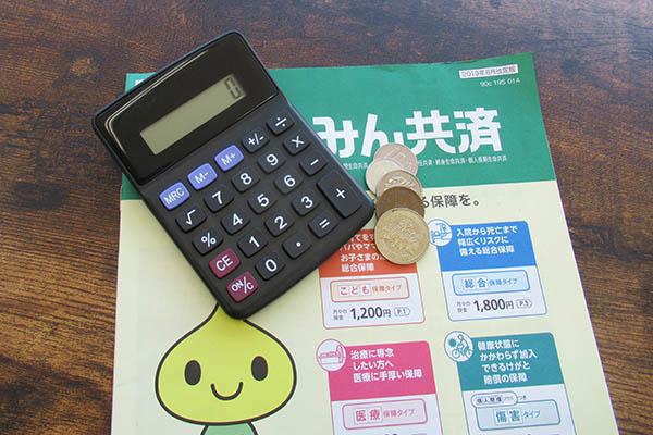 共済組合のパンフレットとお金と電卓